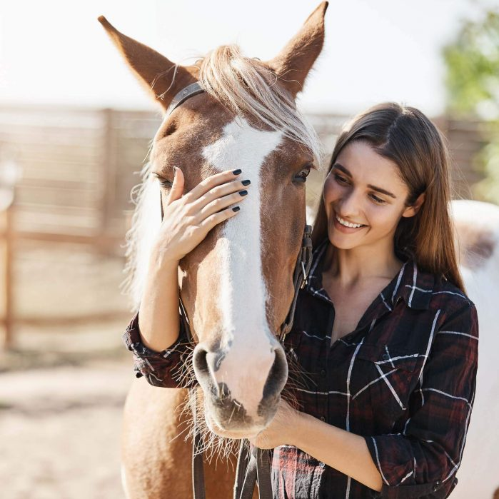 Young lady petting her horse